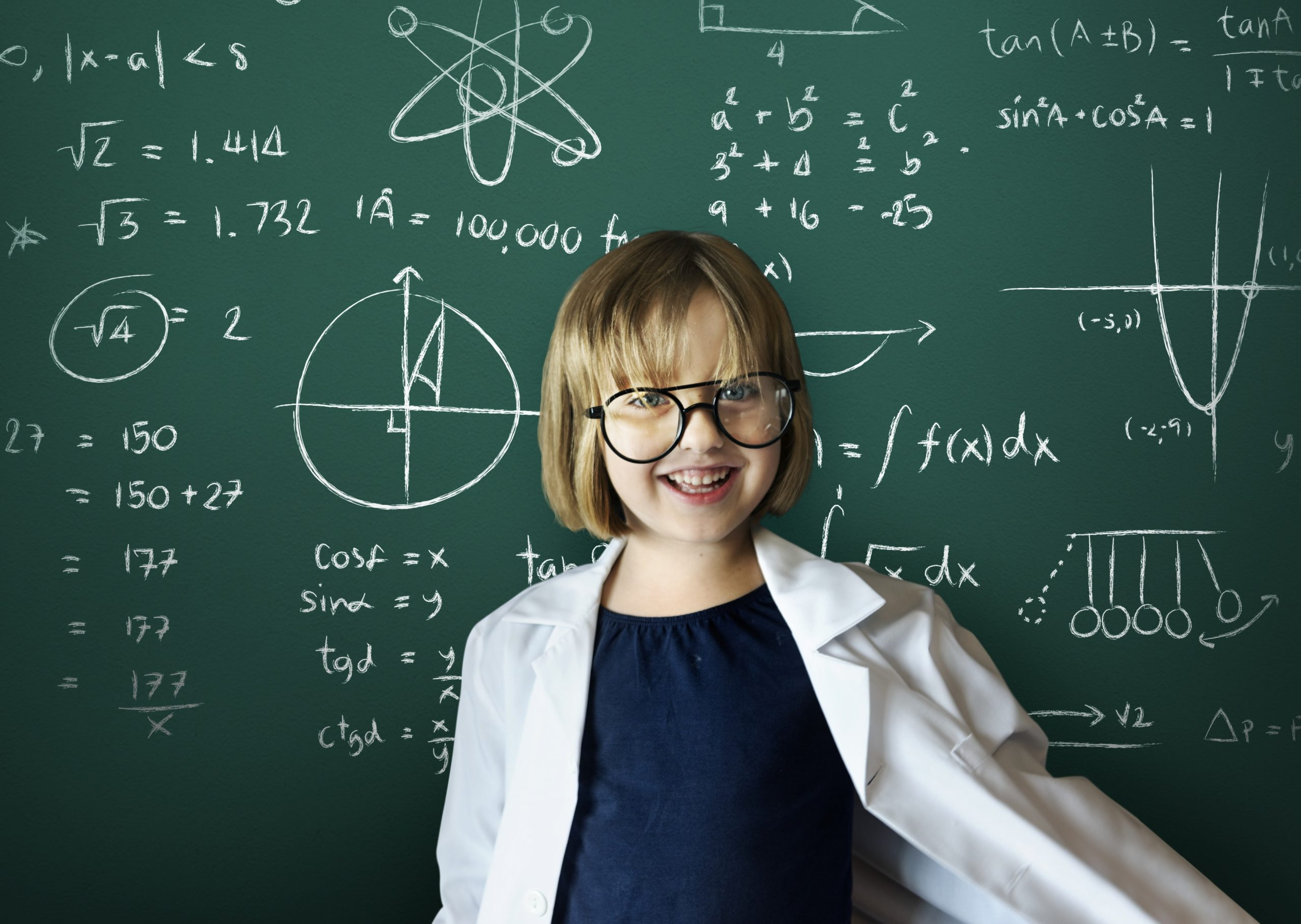 girl having fun with maths on a chalk board